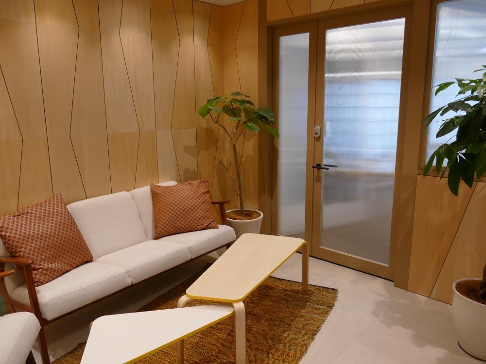 シェアオフィス「social hive HONGO」の入り口ロビー。ここはさまざまな業種のスタートアップ企業が入るシェアオフィスで、大部屋の中に十数人が座れる大きなデスクが1つと、ソファや棚があるだけのシンプルな内装で、奥には大きな窓があり開放感がある