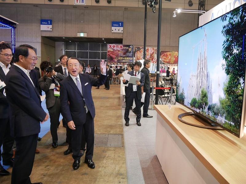 シャープブースで、パナソニックの津賀社長に8Kテレビを説明するシャープの西山博一執行役員