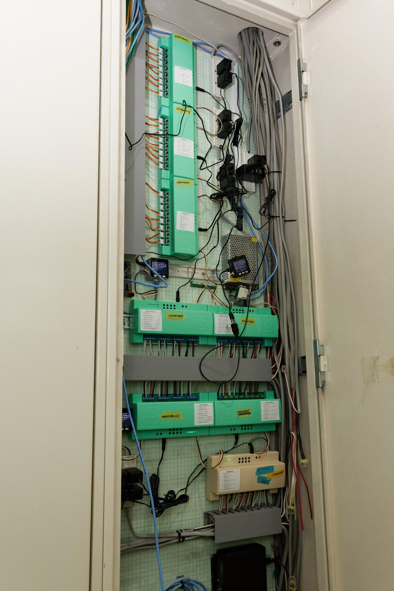 配電盤に設置された自作のHA機器類。緑色のボックスと小さな液晶モニター付きのデバイスがそれ