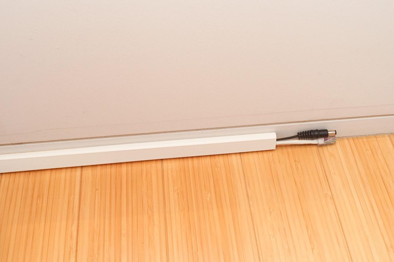 Lサイズは、ACアダプタのケーブルも一緒に入る。裏には両面テープが付いていて、壁の巾木などに接着できる