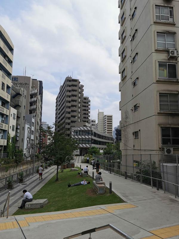 画面奥、側面に縞模様が描かれてるのが渋谷ブリッジのA棟。写っていないが右奥にさらに大きなB棟がある。地下化した東急東横線の渋谷~代官山間の跡地に建てられているので、手前の遊歩道含めて細長い