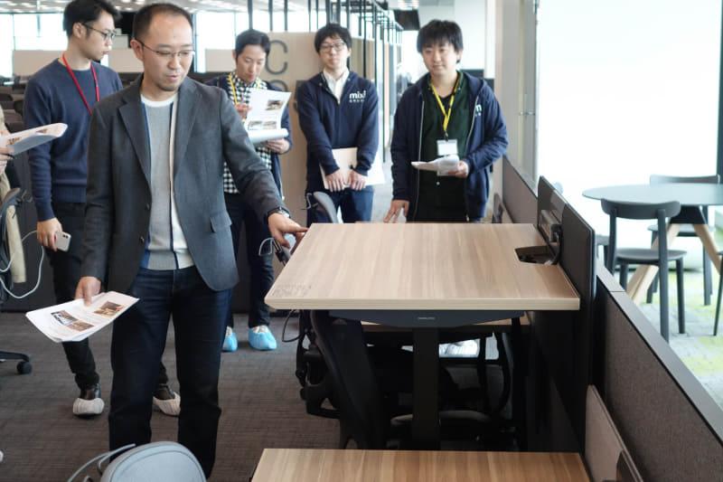 昇降デスクを説明するミクシィの大澤弘之CFO