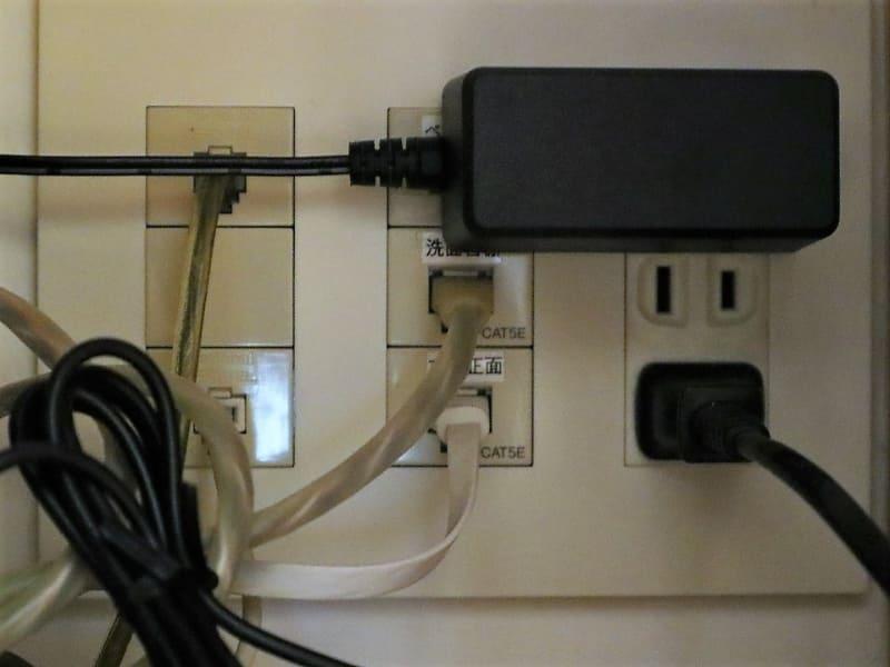 「WSR-1800AX4」のACアダプターを壁面の電源コンセントに挿した状態。左側にある宅内有線LANのポートを塞いでいる