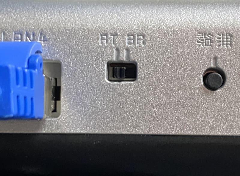 ルーター機能の有効/無効(ブリッジ接続)の切り替えは、本体に備えられたスイッチで設定するアクセスポイントが多い。写真はNECプラットフォームズの「Aterm WX6000HP」で、背面のスイッチを「RT」にするとルーター機能が有効に、「BR」にすればブリッジ接続になる