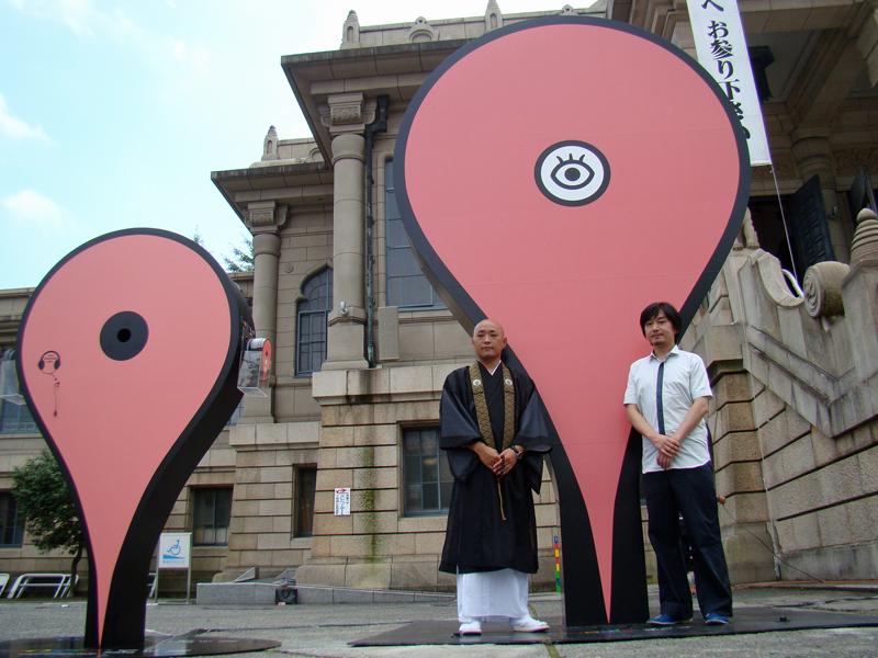 駅構内に設置するピンと、築地本願寺に設置する巨大ピン。その前に立つのは、築地本願寺の平井祐善氏(左)と建築家の平田晃久氏(右)