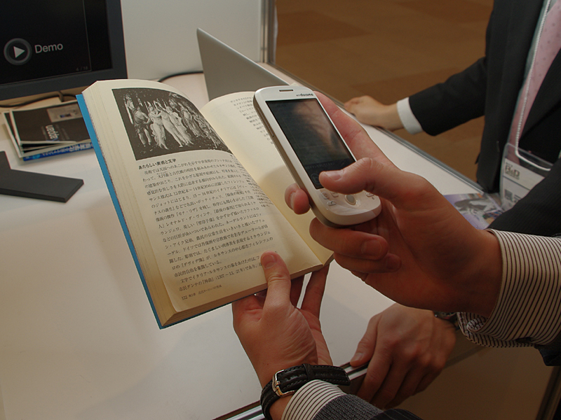 携帯電話で撮影した本に関連したコンテンツを表示できる。Android搭載の「HT-03A」にアプリをインストールしてデモしていた