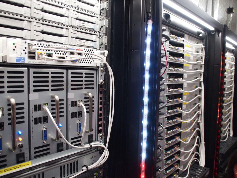 DC給電のサーバーが並ぶ。左のラックが、上からNEC Express5800、NTTデータPRORIZE-DC、NTTデータ Lindacloud。右のラックが、さくらインターネットの自作サーバー。ラック横のLEDも同じDC12Vで光っている