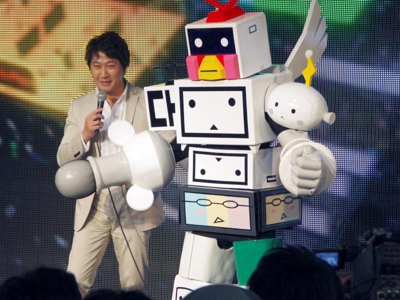 ニワンゴ社長の杉本誠司氏と、ニコニコ超会議広報キャラクターの「ニコニコ超会金」