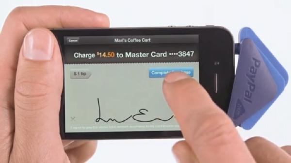 クレジットカードをスキャンした後、顧客がiPhoneのタッチ画面上でサインをする