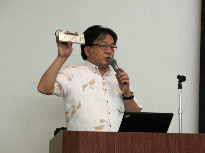 ディジタルアシスト代表取締役の永田健児氏。手に持っているのがシャープ「ポケット電訳機 IQ-3000」