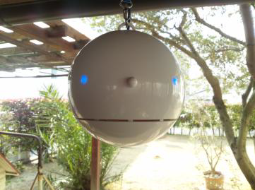 「ポールンロボ」は直径15cmの球体で、人の呼吸と同じ量を吸引するように設定されており、実際に人間が空気中で吸い込む花粉量を計測できるという。花粉の飛散量によって、ロボの目の色が白(1日あたり0~29個)から青、黄、赤、そして紫(同300個以上)へと5段階に変化する仕組み。花粉の飛散量だけでなく、気温、湿度、気圧、空気中のダストも観測。今年は、春先に多い黄砂や火山灰などの浮遊粒子のモニタリングを強化するほか、昨年に引き続きPM2.5も試験的に観測する予定