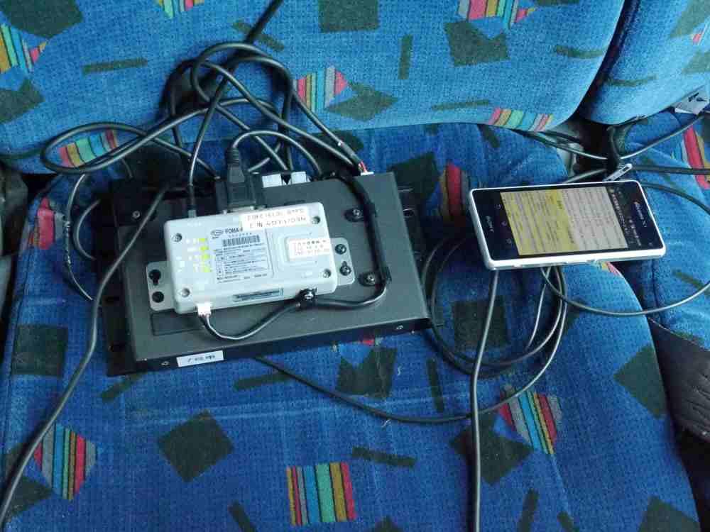 車内にはQZSS受信機からの情報を受け取るAndroidスマートフォン(右)とバスロケの送信機(左)が設置