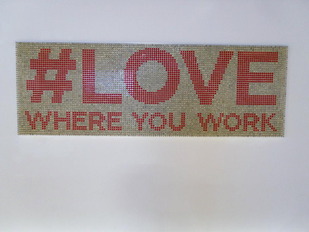 壁に配置された「#LOVE WHERE YOU WORK」というアート