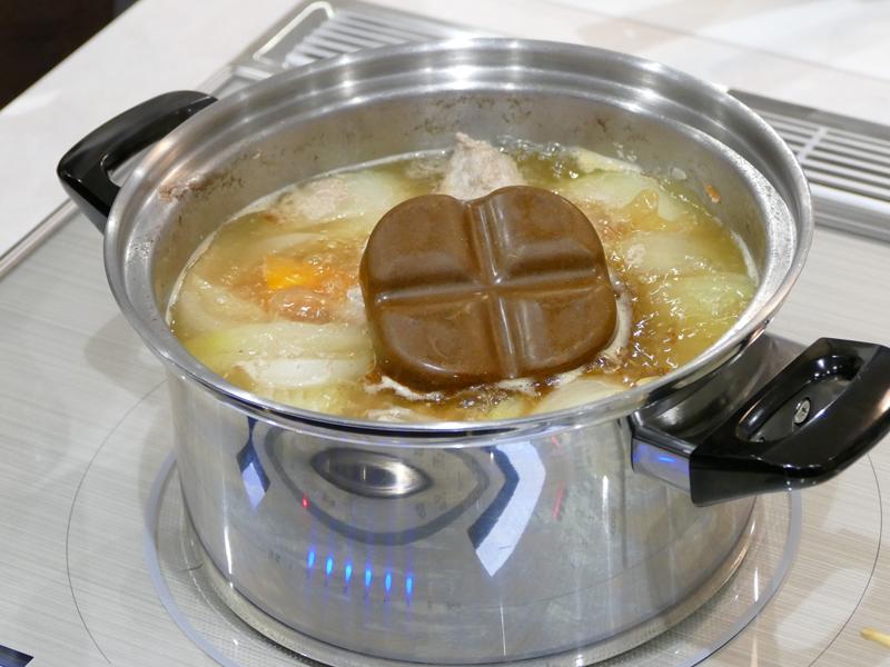 会場での調理実演。カレーのルーを小さく割ることなく、大きいまま鍋に入れる