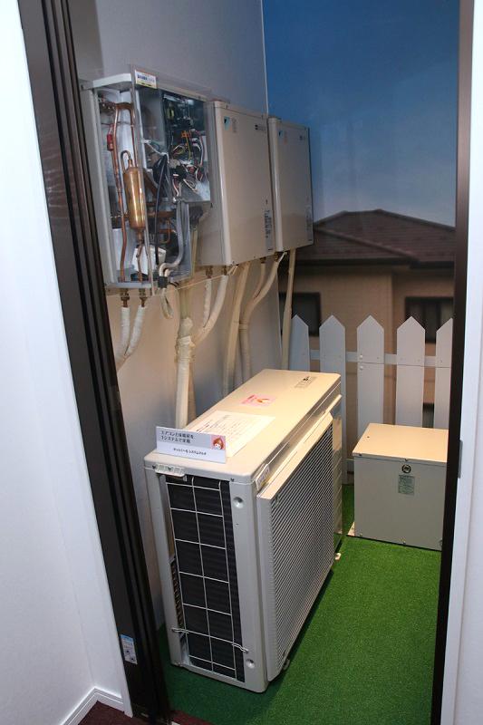 広さや出力にもよるけど、エアコンの室外機とほぼ同じ大きさのもので対応可能。上のボックスは、温水の循環器