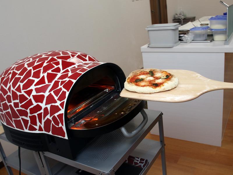 焼きたてのピザを、タイガー特製の窯から取り出す!