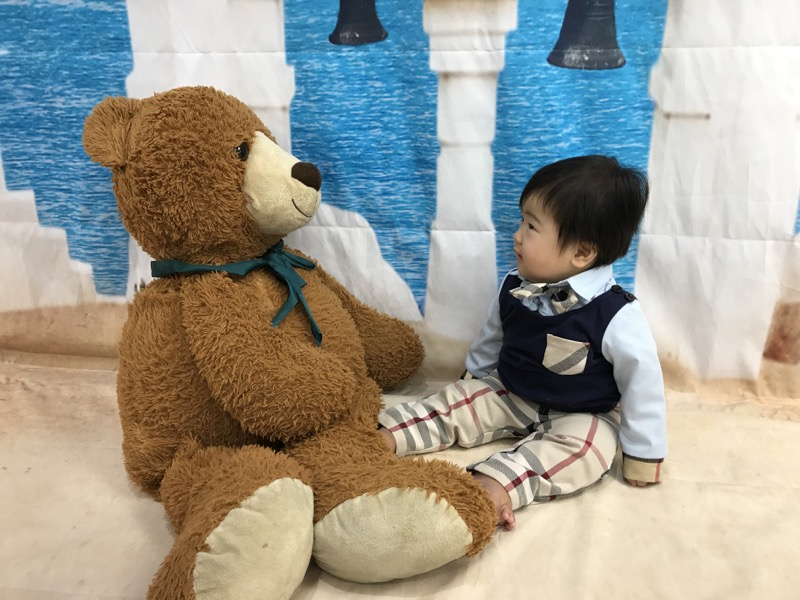 よくわからないまま着替えさせられ、クマのぬいぐるみと対峙する息子