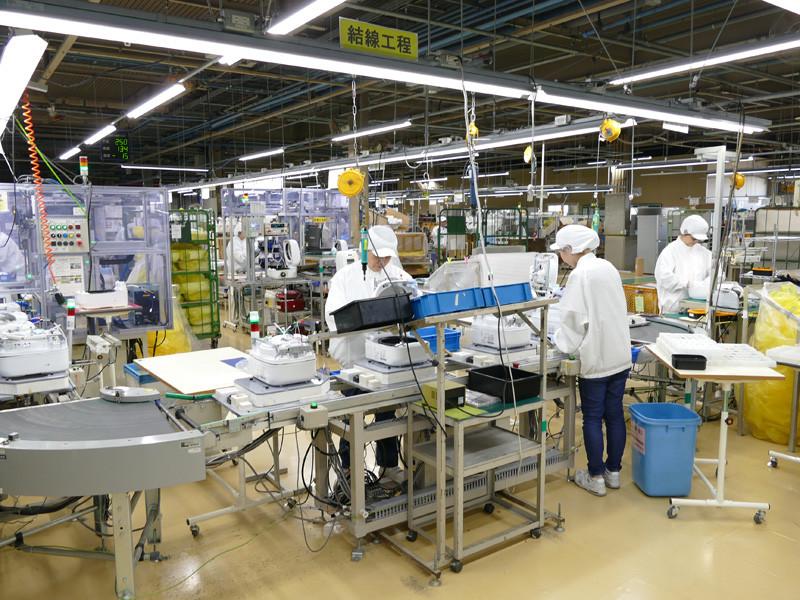 工場内の結線工程を担うところ。作業する人々は、髪の毛をすべて覆う帽子と、本体に傷がつくのを防ぐためにファスナーのない白衣を着用しています