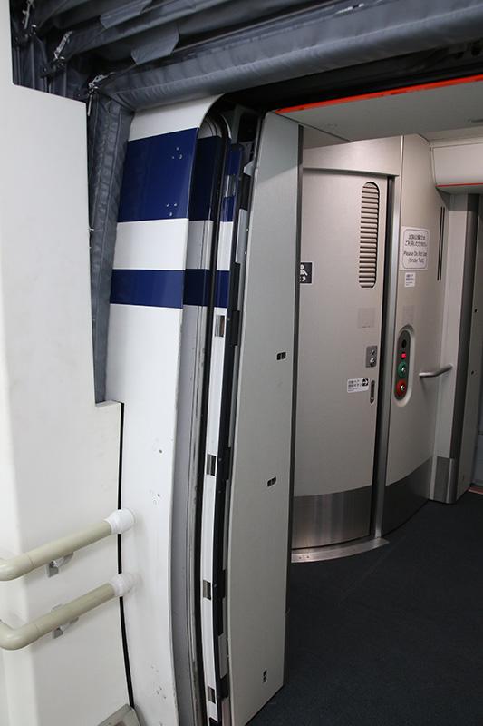 リニアの乗降用ドア。新幹線と同じ引き込み式のプラグドアになっていて、車内の気密を保つ。MLX01では上に跳ね上げるドアもあったが、最終的には引き込みドアになったようだ。奥にはトイレも見えるが、試験設備のため使用できない
