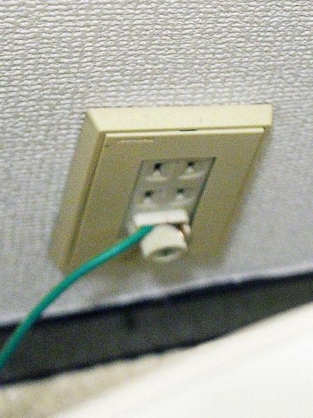 露出した銅線を壁面のアース端子に接触させて接続
