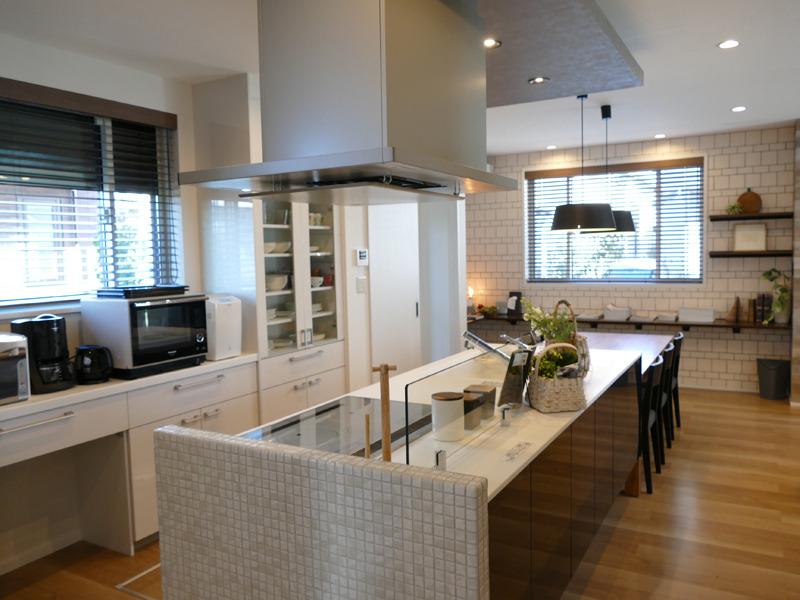 開放的なアイランドキッチンを備えたダイニング・キッチン。パナソニックの最新調理家電がずらりと並ぶ