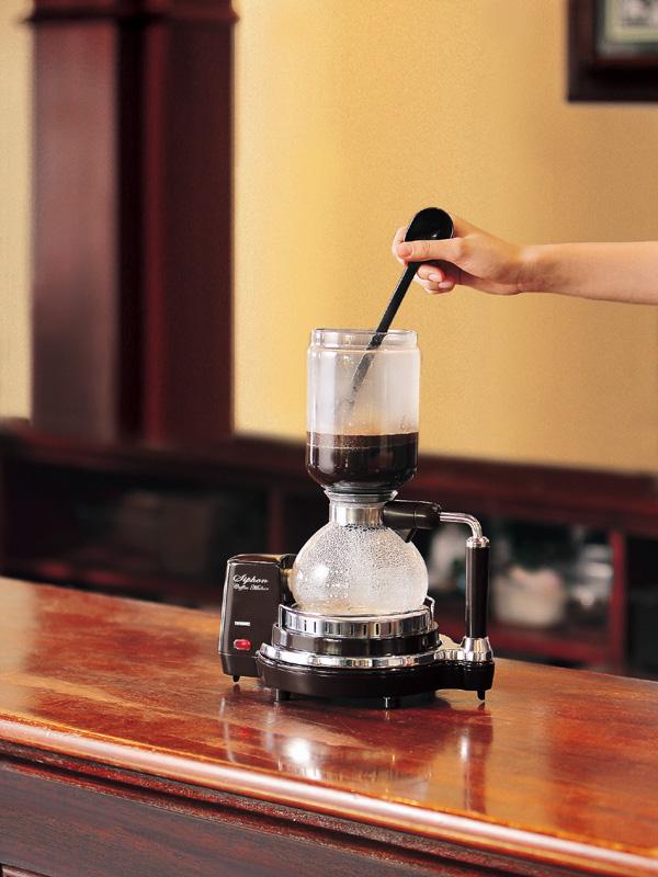 お湯が漏斗に挙ってきたら、ヘラでコーヒー粉をほぐしばがら、ゆっくりとかき回す