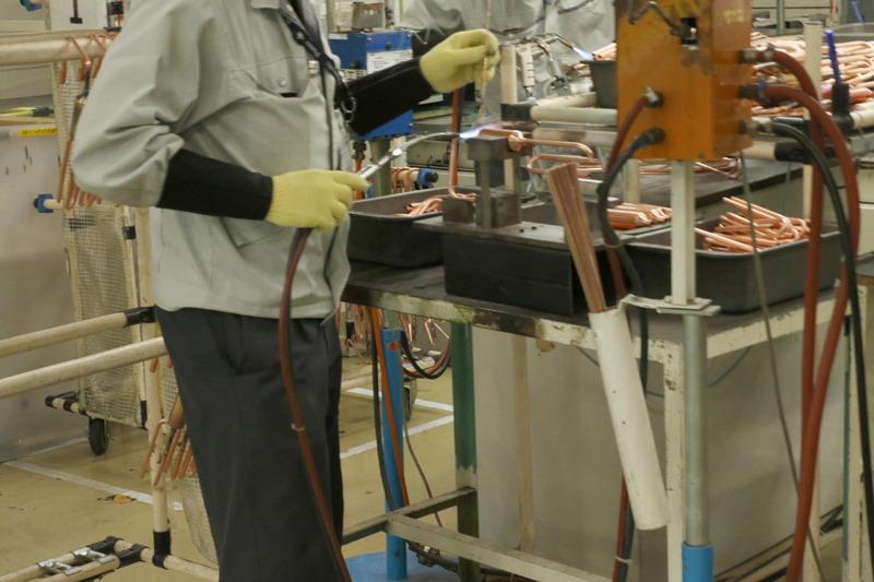 こちらはたぶん室外機のコンプレッサ周りの配管。バーナーの反対に持っている棒がロウと呼ばれるもの。要は電子回路作るときの半田と一緒