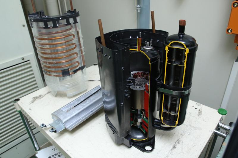 断面が見えているのがコンプレッサ。モーターでガスを圧縮するので熱が発生。コンプレッサをU字に囲むのがエネチャージシステム。コンプレッサの廃熱を蓄熱材に蓄積。霜取り運転中の熱源にする