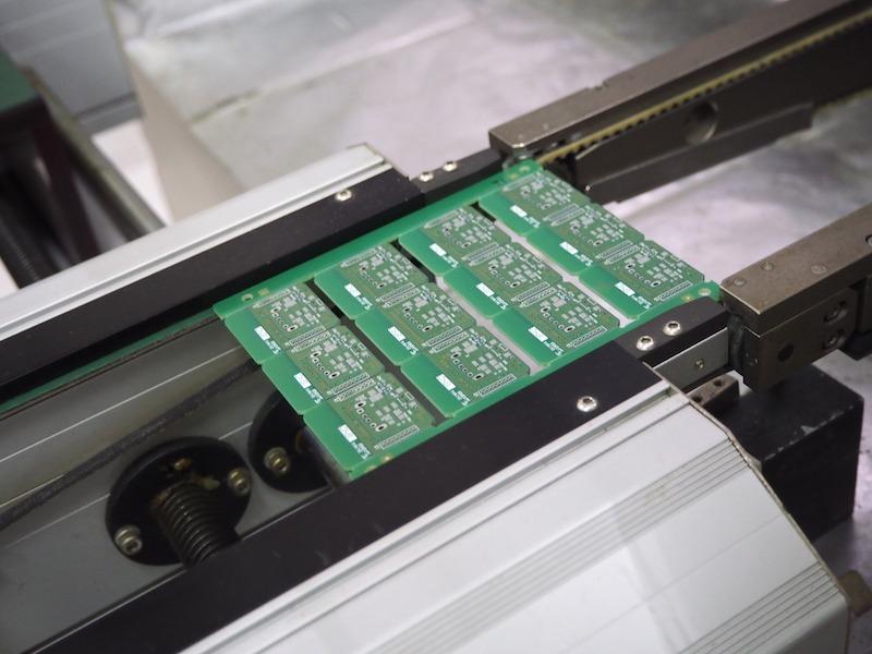 次々と電子部品が実装された基盤が機械から出てくる