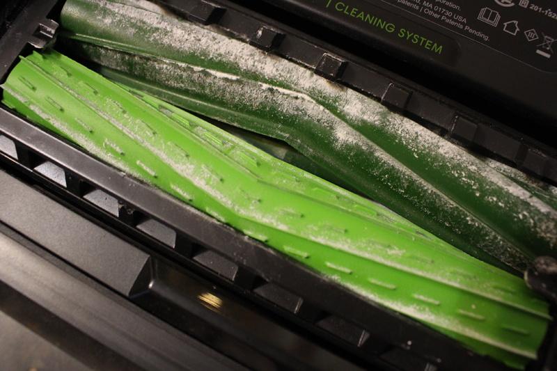 小麦粉を吸った後のデュアルアクションブラシ。濃い緑のブラシの羽根に、床からかき取った小麦粉がついている