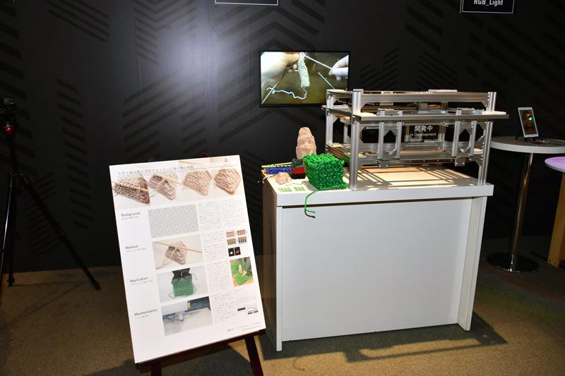 3Dプリンターのようだが、さまざまな素材を編み込むことで構造物を作る「Solidknit」プロジェクトの展示