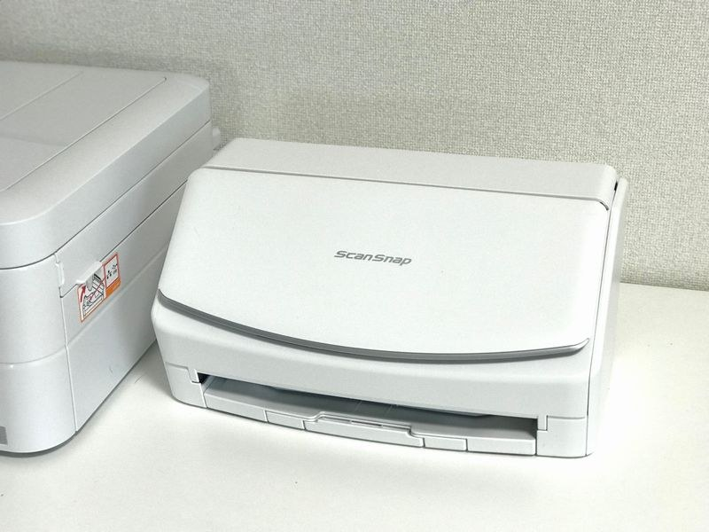 PFU パーソナルドキュメントスキャナー「ScanSnap iX1500」。隣に置いてあるプリンター(複合機)と比較してもかなり小さく感じる