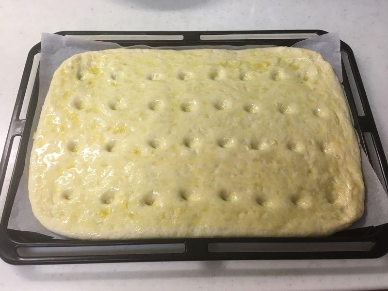 角皿いっぱいに生地を広げて伸ばし、オリーブオイルを塗ったら、指で穴をあける。オーブンペーパーを敷いて作業するとやりやすい