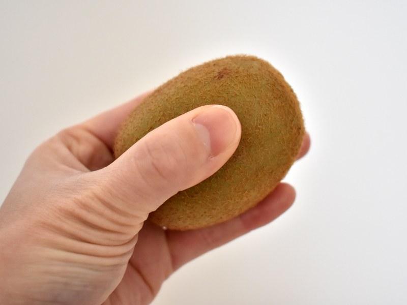 果実を手で包み、指で軽く押して確かめる