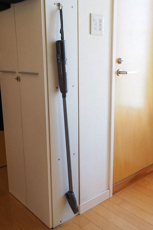 本体後部端のリストストラップを使い、フックに吊して保管している様子。スティック掃除機状態でも吊しての保管ができます