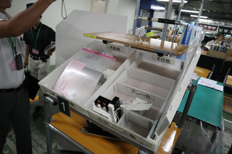 専用の特大部品皿に必要な部品を棚からピックアップ。このとき手持ちのタブレットから、ピックアップする部品の指示がある。タブレットは製品完成まで持って回る