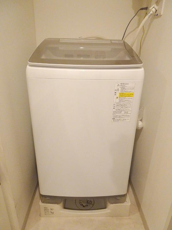 AQUAの縦型洗濯乾燥機「AQW-GTW100H」。好みを選ばないホワイトの本体に、ガラストップの天板を採用し、操作部などの一部にシルバーをアクセントとして施したデザインは、シンプルながらも洗練されている