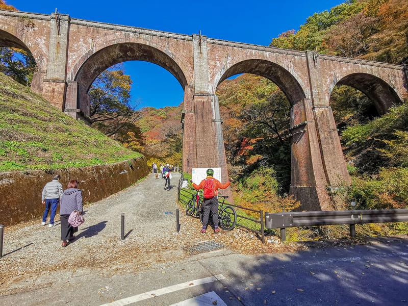 めがね橋前で絶景に感謝を捧げるポーズをキメる筆者。めがね橋は日本最大の「煉瓦造りのアーチ橋」です。かつては登坂力のある「アプト式鉄道」がこの上を走っていましたが、現在は廃線で、観光スポットのひとつになっています。自転車をめがね橋奥の林道空地に駐車し、めがね橋の上まで徒歩で上ります
