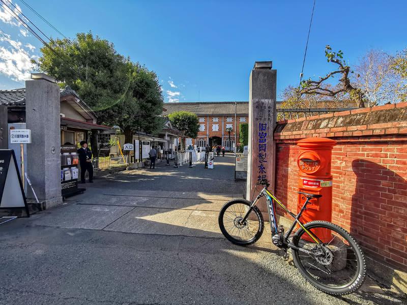 """トランスポーターで移動し、富岡製糸場近くの<a href=""""http://www.tomioka-silk.jp/tomioka-silk-mill/access/parking.html"""" class=""""n"""" target=""""_blank"""">富岡駅東駐車場</a>という無料の観光用駐車場に駐めました。富岡製糸場近くではありますが、製糸場までの距離は約1km(徒歩約20分)です。富岡製糸場周辺の道は狭く、クルマでは入れない場所もありますので、やはりこういった古い町の観光はe-bikeが好都合です"""