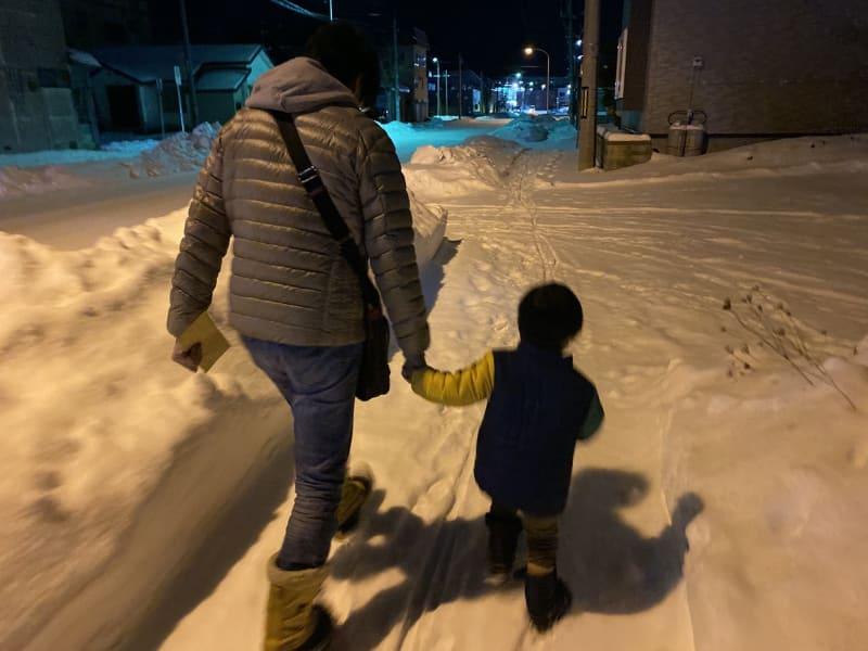伯父に手を引かれ雪道を歩く
