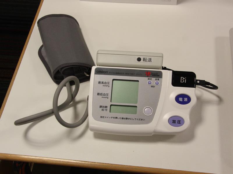 オムロンヘルスケアの血圧計「Continua対応血圧計」(試作品)。パソコンへデータを送る場合は、「転送」ボタンを押す