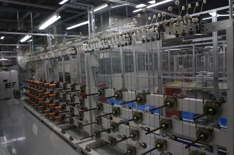 ここだけ家電の工場ではなく、紡績工場の様相。白いプーリーに引っかかっている細い電線が見えるだろうか? これを奥に送りよじって1本の電線にする