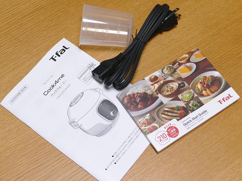 電源コードの長さは1.5m。計量カップは炊飯用。210種類の内蔵レシピの、2人用・4人用に対応した材料表がまとまっている冊子も付属している