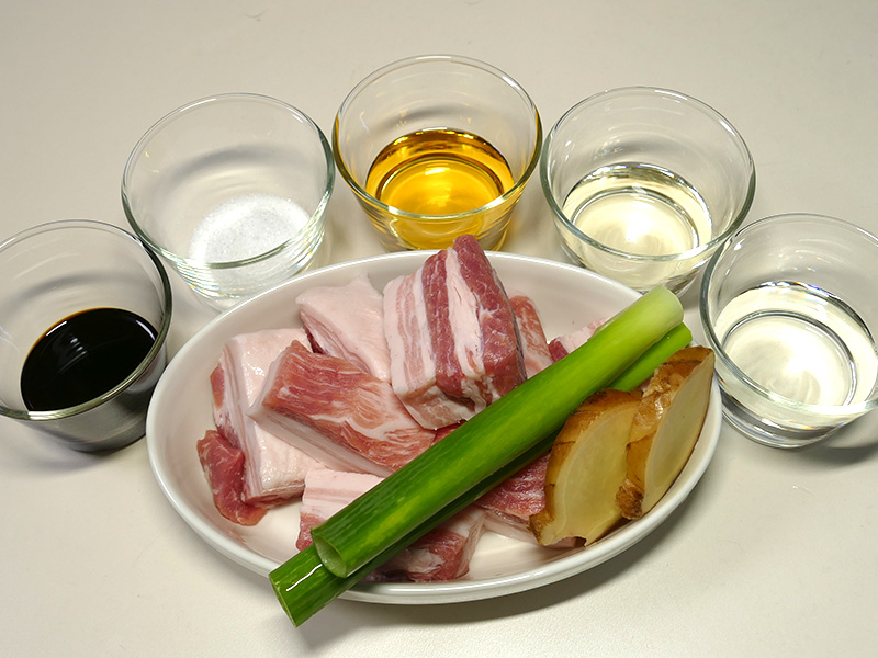 豚肉の角煮2人分の材料は、豚バラ/ねぎの青い部分/しょうがスライス。調味料として、しょうゆ/砂糖/みりん/酒/水