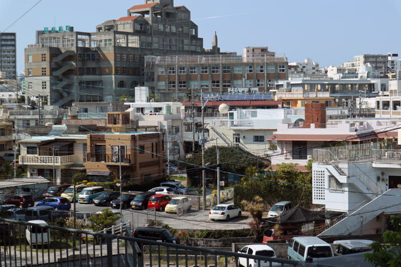沖縄の多くの住宅は、コンクリート製で平らな屋根か、斜めの屋根がついている。本州のような三角屋根の住宅は少ない