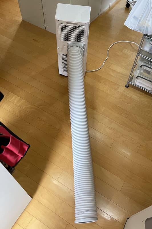 付属の排気ダクトを本体に接続した様子。本体背面排気口からの熱を帯びた排気を、窓などから室外に放出するためのフレキシブルパイプです。排気ダクトの長さは35〜145cmに調節でき、ダクト直径は13cm