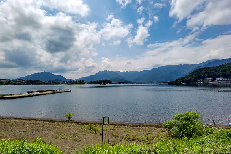 河口湖の湖畔。ホテルが立ち並ぶ河口湖東側にある観光用駐車場にトランポのクルマを駐め、e-bikeを下ろします。梅雨の合間で、天気は晴れたり曇ったり
