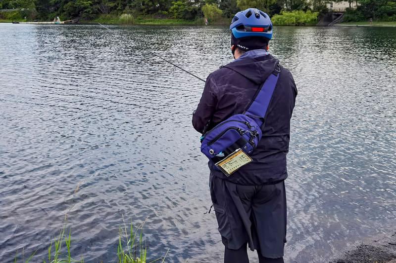 """サイクルヘルメットをかぶってフィッシングな筆者。ちょっと目立ってますが、<span class=""""em underline-yellow"""">自転車のウェアや装備って、釣りにもそのまま使えるものが多いような気がします</span>。特にフィッシングのウェア類はUVカットだったり速乾だったりして、サイクリングにそのまま使えるものも多い"""