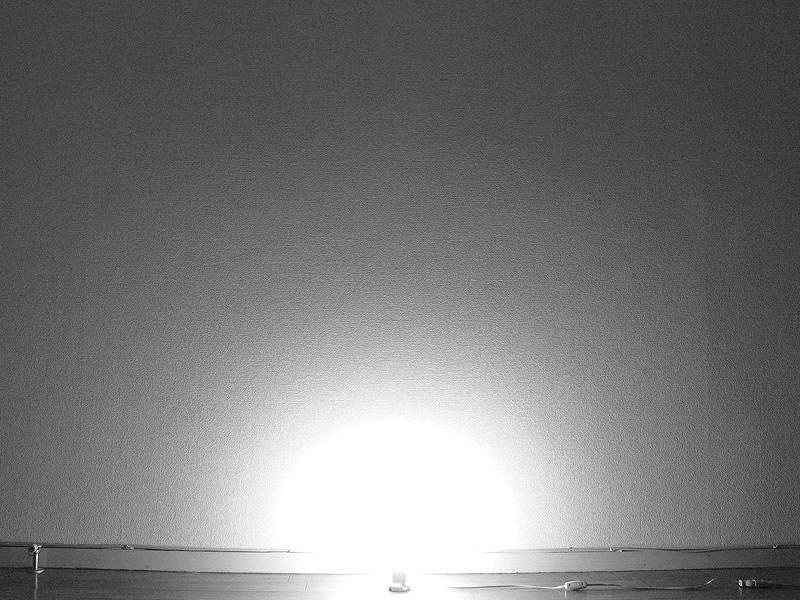 電球形蛍光灯の光の拡散は、白熱電球のそれとほとんど変わらない。根元に回路部があるため、光が床面に回り込まず、多少ソケットが見える(点灯から20分間放置し、光が安定したところを撮影)