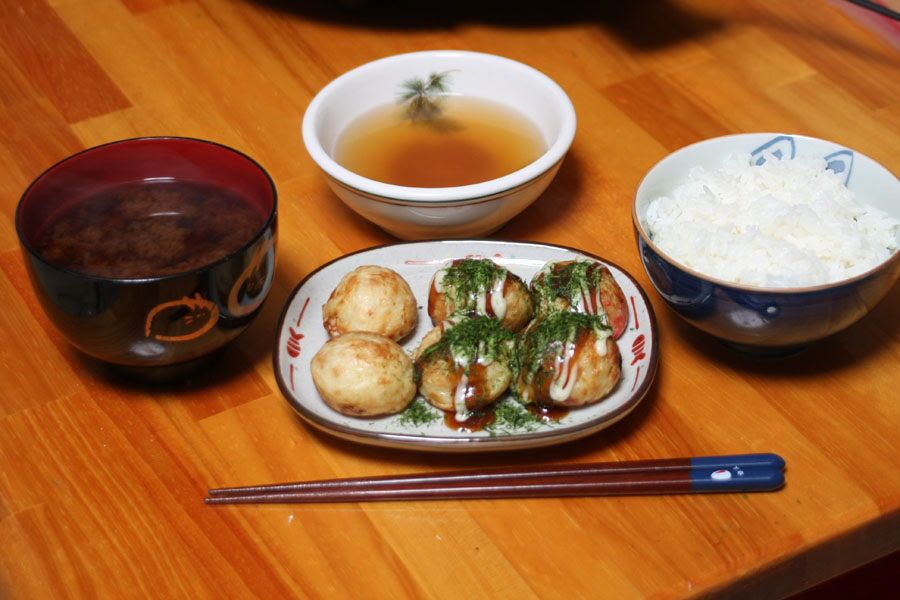 ごはんと味噌汁とたこ焼きで夕食。画面奥にあるのは、かつおだしに塩としょうゆを加えた明石焼き風のタレ